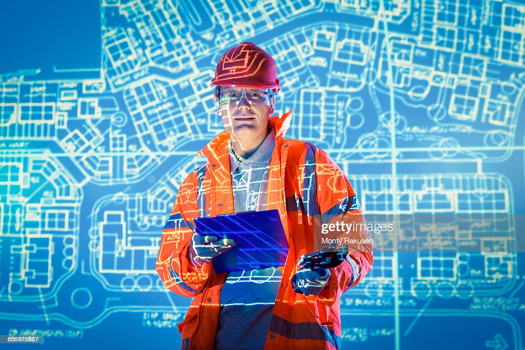 Engineer with digital tablet and projected plans, portrait : Stock Photo