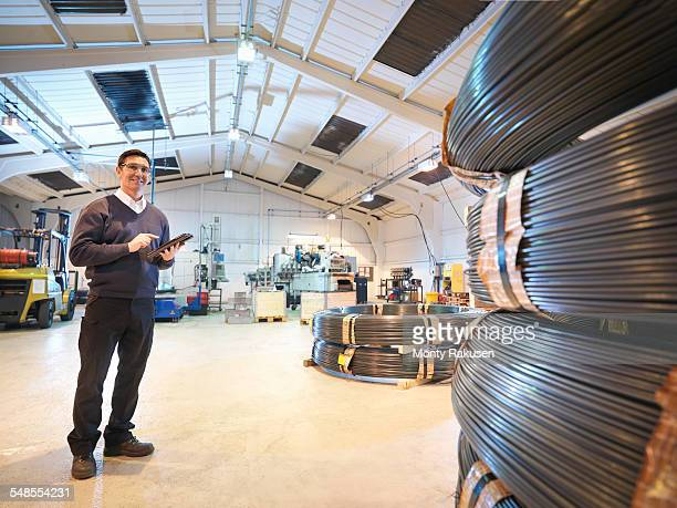Engineer with digital tablet in automotive parts factory, portrait
