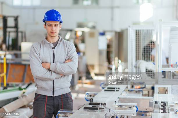 Engineer with hardhat standing near production line with arms crossed