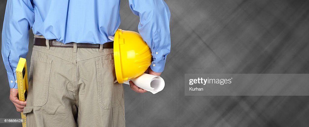 Engineer with helmet and blueprint. : Stock Photo
