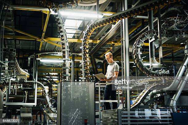 Engineer with laptop in a factory between machines