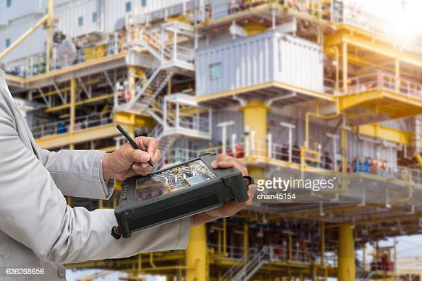 Engineer with large oil and gas industrial background with the labtop tablet