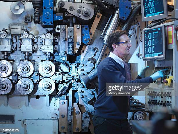Engineer with machinery in automotive parts factory