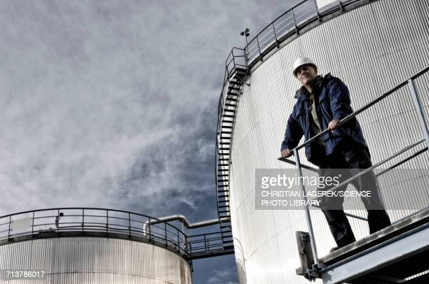 Engineer with oil storage towers