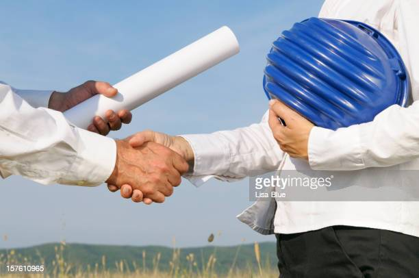 Engineer with Plan Handshaking in a Wheat Field