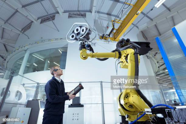Engineer with robot in robotics research facility, low angle view