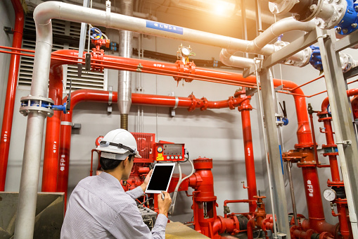 Engineer with tablet check red generator pump for water sprinkler piping and fire alarm control system. 1097682848