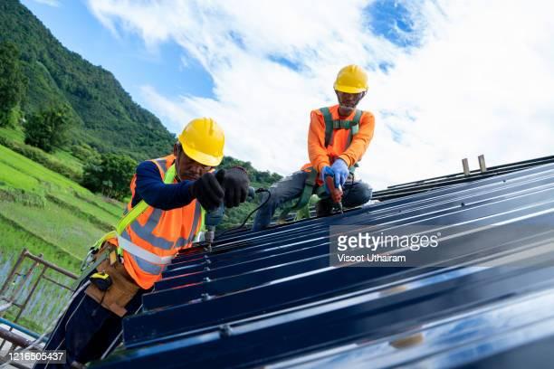 engineer worker wearing safety line working working installing new roof. - beddengoed stockfoto's en -beelden