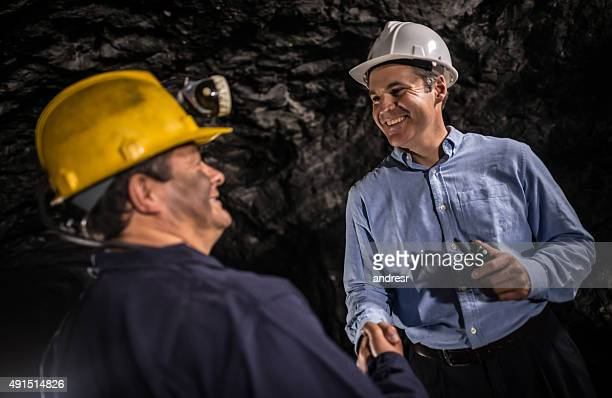 Engineer working at a mine handshaking a worker