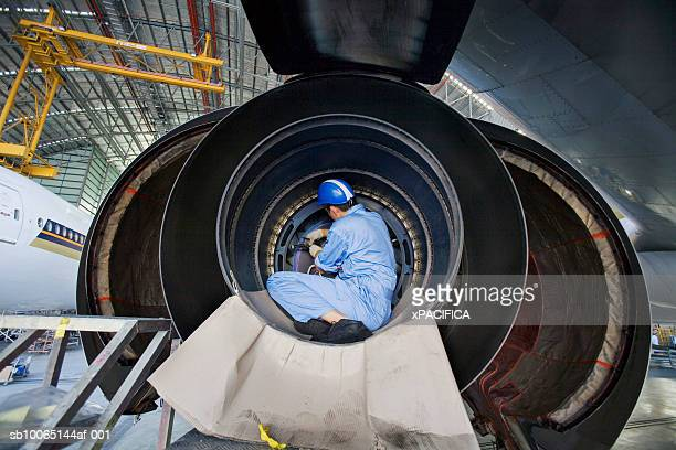 Engineer working at aviation maintenance facility, rear view