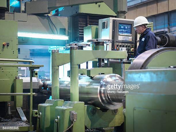 Engineer working at lathe in engineering factory