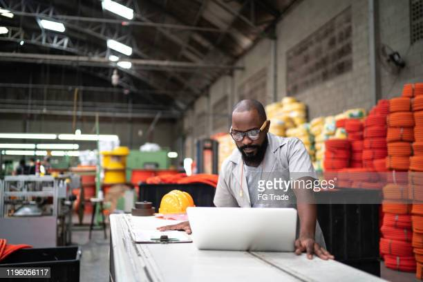 engineer working at the factory using laptop - manufacturing stock pictures, royalty-free photos & images