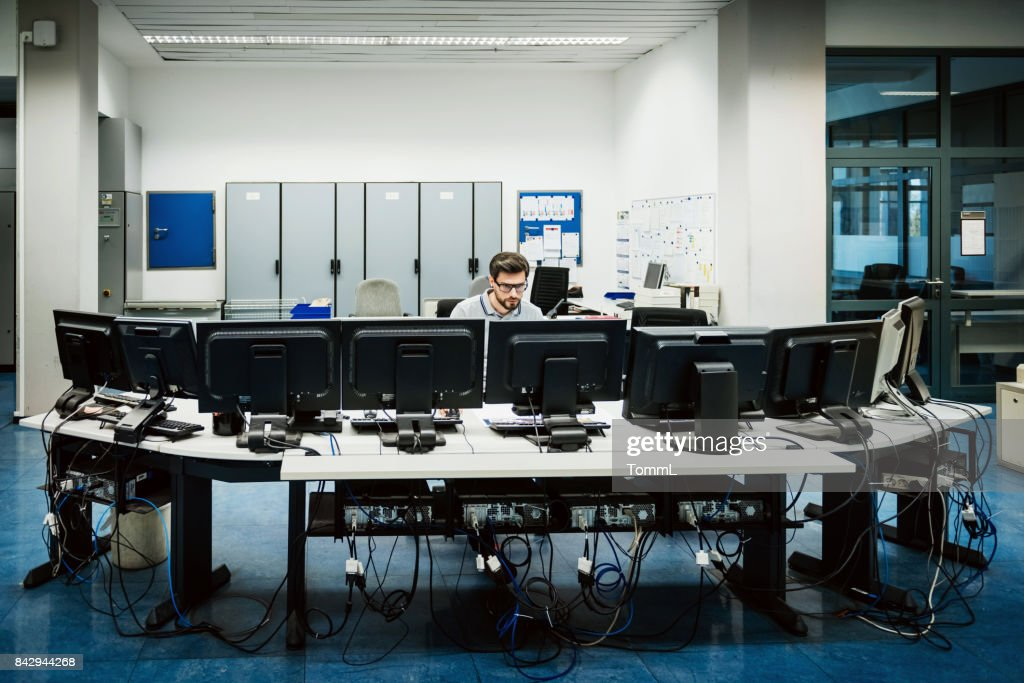Engineer working in big control room : Stock Photo
