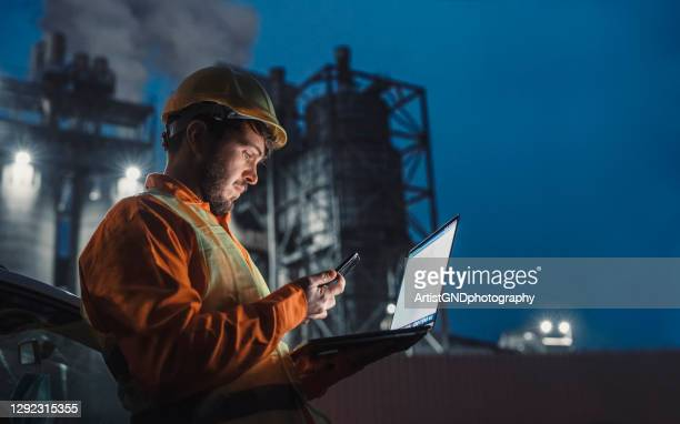 engineer working nightshift and using technology in front of petroleum industrial factory. - making stock pictures, royalty-free photos & images