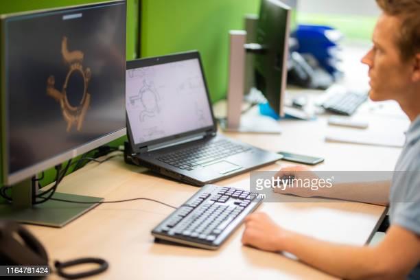 ingenieur, der an einem computer arbeitet - rechnerunterstütztes konstruieren stock-fotos und bilder
