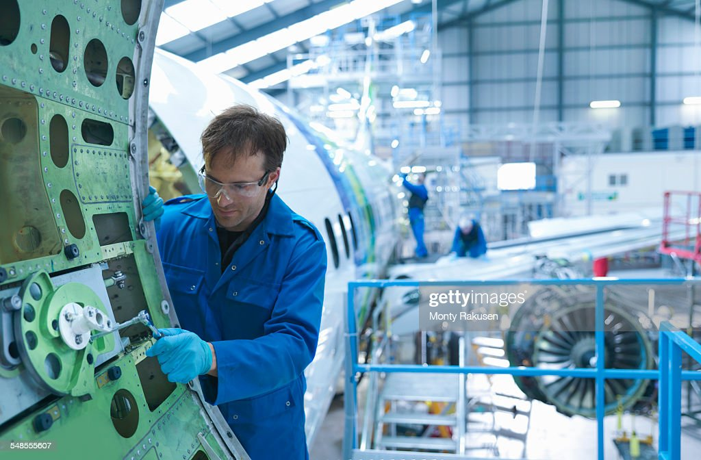 Engineer working on aircraft door in aircraft maintenance factory : Stock Photo