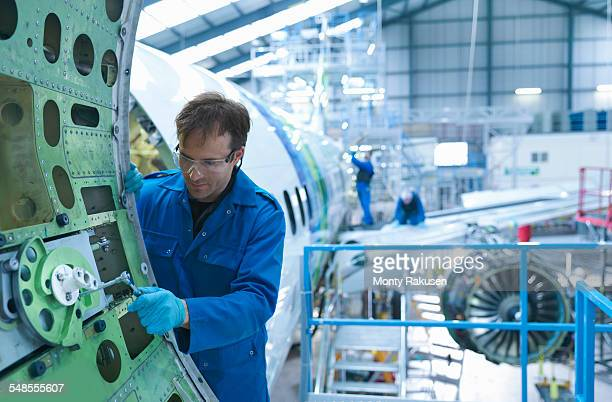 engineer working on aircraft door in aircraft maintenance factory - cargo airplane - fotografias e filmes do acervo