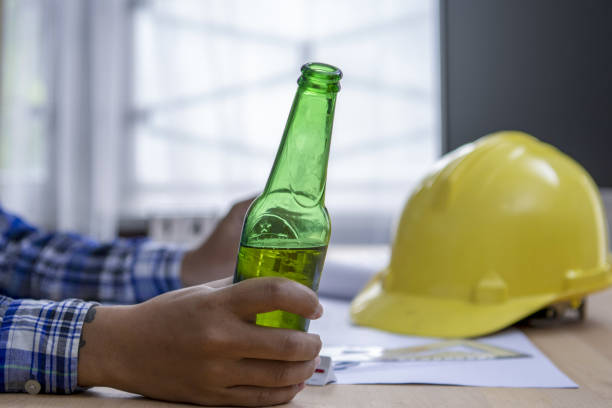 Engineer working on architectural project at construction site at desk.He hold a bottle of drink.