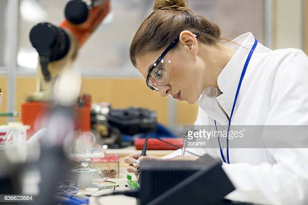 Engineer working on circuit board at desk