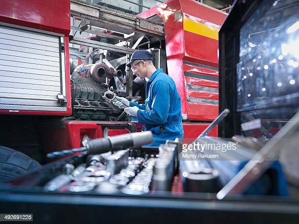 Engineer working on engine in truck repair factory
