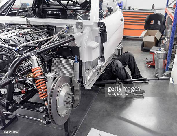 Engineer working under car in racing car factory