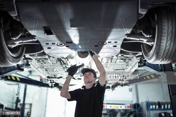 engineer working underneath car on lift in car service centre - mode of transport stock pictures, royalty-free photos & images
