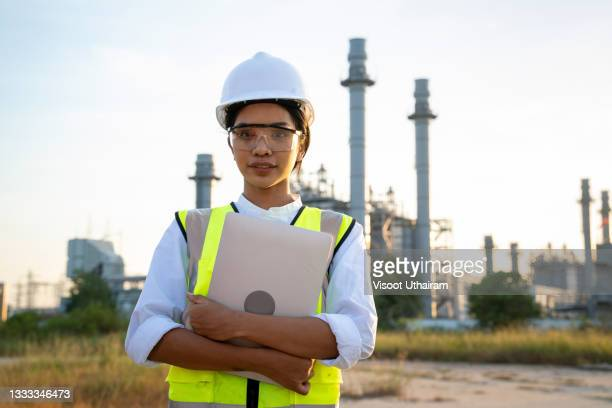 engineer working wearing safety helmet use notebook working and checking work in front of an oil refinery. - greenpeace stock pictures, royalty-free photos & images