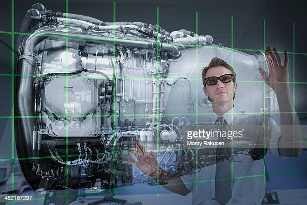 Engineer working with 3D display of Jet Engine, seen through interactive screen