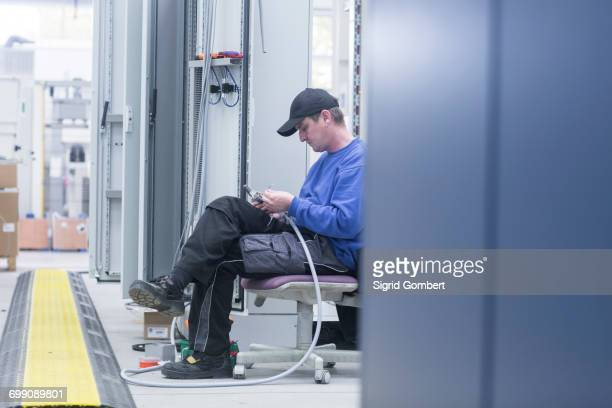 engineer working with electrical components in engineering plant - sigrid gombert - fotografias e filmes do acervo