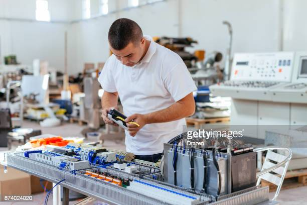 Engineer working with fuses and power supply cables for production line engine