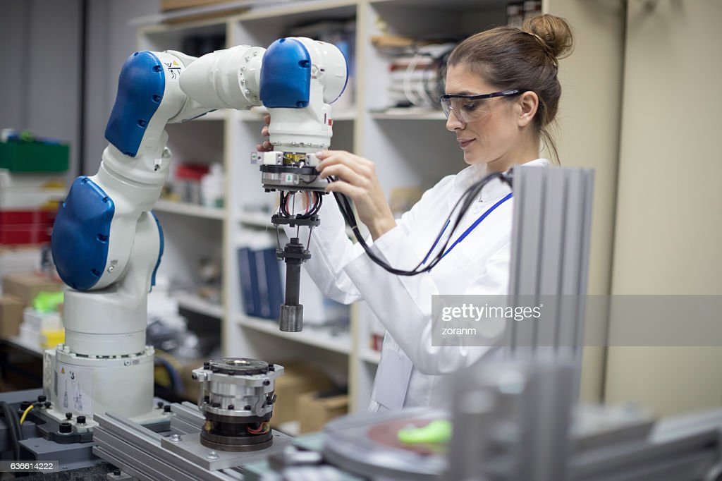 Engineer working with robotic arm : Stock Photo