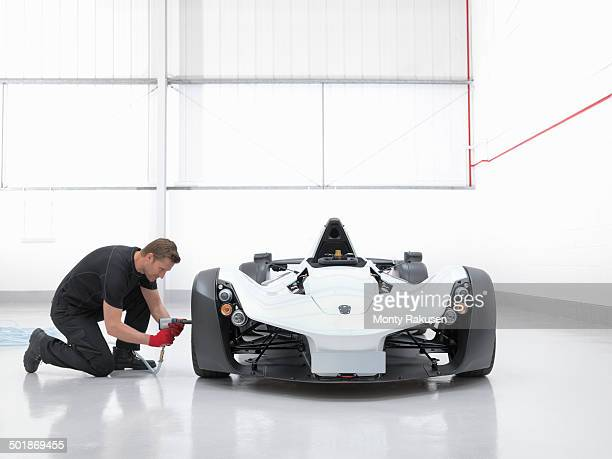 Engineer working with supercar in factory