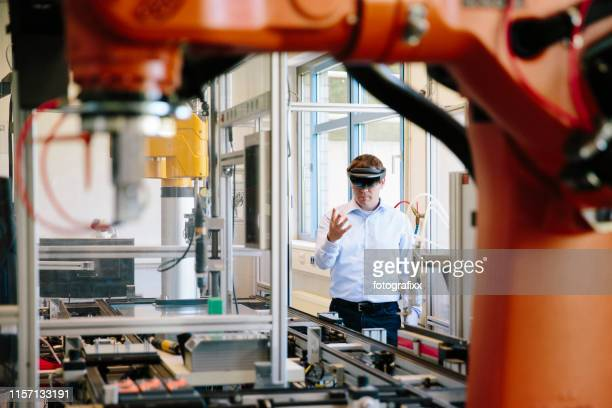 engineer works with a hololens: place a virtual robotic arm into the production line - realtà aumentata foto e immagini stock