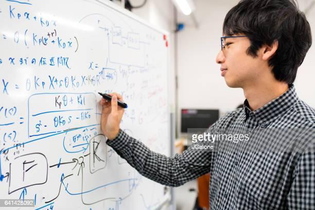 ホワイト ボードの方程式を書くエンジニア