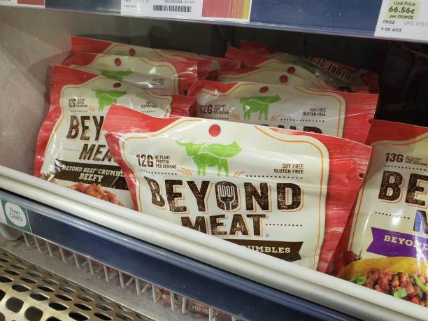 Engineered plant-based frozen crumbles from food company Beyond Meat are visible on shelves among other meat alternatives at a grocery store in San...