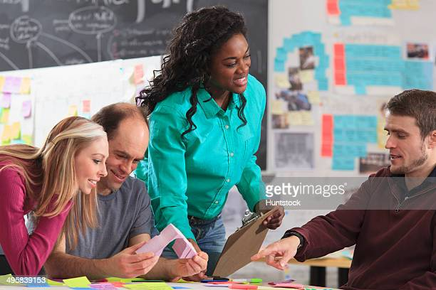 engineering instructor demonstrating 3d shape to students in ideation lab, one man with spinal cord injury and other one with aspergers - autism spectrum disorder stock photos and pictures