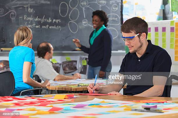 engineering instructor working on flowchart on blackboard while students working on project, one man with spinal cord injury and other one with aspergers - autism spectrum disorder stock photos and pictures