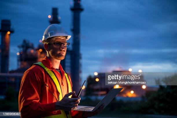 engineering is use notebook check and standing in front of oil refinery building structure in heavy petrochemical industry - petrochemical plant stock pictures, royalty-free photos & images