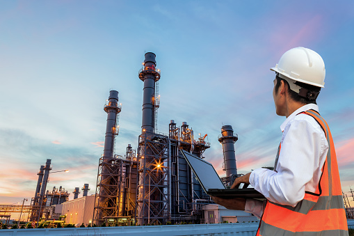 Engineering is use notebook check and standing in front of oil refinery building structure in heavy petrochemical industry 922601466