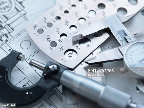 engineering measurement, dial calipers sitting on a steel rule with micrometer and engineering drawings - accuracy stock pictures, royalty-free photos & images