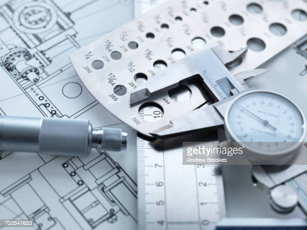 engineering measurement, dial calipers sitting on a steel rule with micrometer and engineering drawings - mechanical engineering stock pictures, royalty-free photos & images