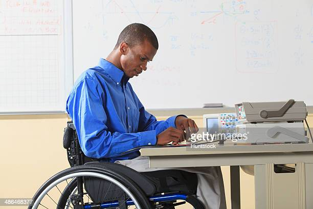 Engineering student sitting in a wheelchair preparing lab experiment with oscilloscope and electronic prototyping breadboard