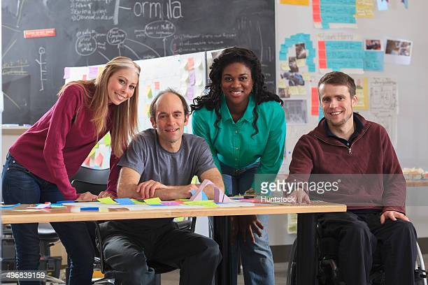 engineering students in ideation lab, one man with spinal cord injury and other one with aspergers - autism spectrum disorder stock photos and pictures
