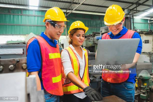engineering team, men and women, wearing helmets, brainstorming projects with laptops in industrial factories - fabricage apparatuur stock pictures, royalty-free photos & images
