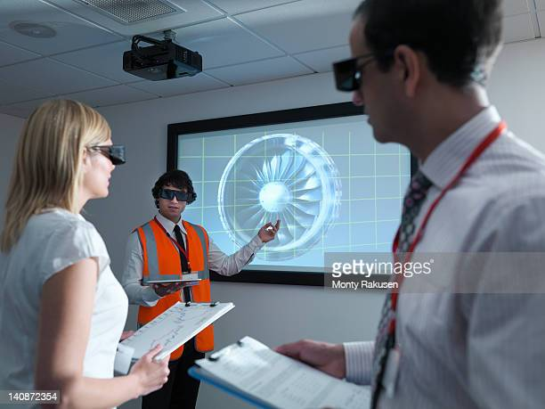 Engineers and apprentice in 3D glasses with clipboards in front of  engine on 3D screen