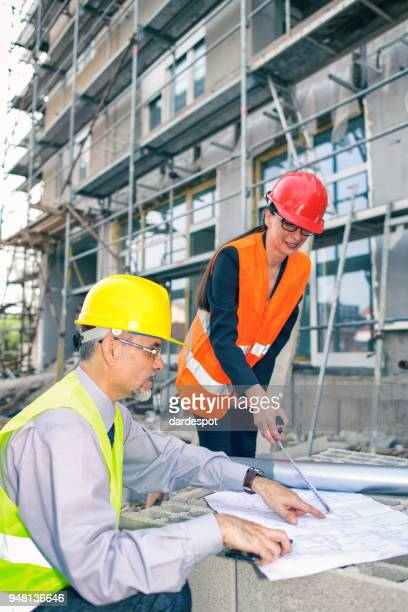 Engineers and architect looking at blueprints on construction site