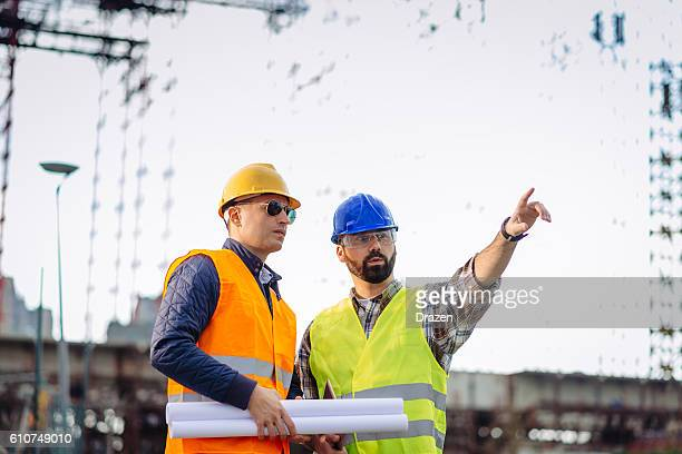 Engineers and construction workers on construction site