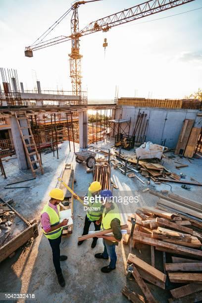 ingenieros y contratistas en el sitio de construcción bajo la grúa - estructura de edificio fotografías e imágenes de stock