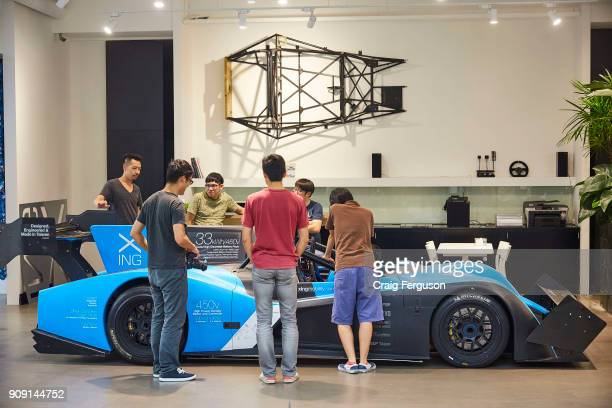 Engineers and designers at Xing Mobility gather around their flagship electric racecar Miss E The company aims to encourage greater adoption of...