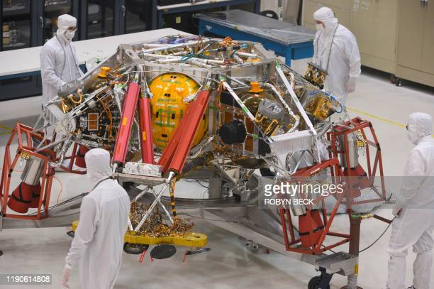 NASA engineers and technicians examine the descent stage of the Mars 2020 spacecraft December 27 2019 during a media tour of the Mars2020 Spacecraft...